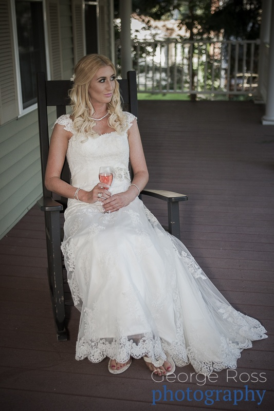 bride sitting on a rocking chair with a glass of wine before the wedding