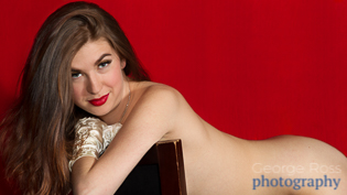 boudoir photograph of a naked woman on a chair with a red background