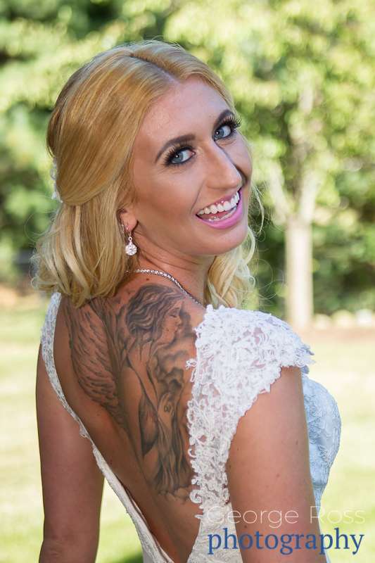 smiling bride with gtatto's on her back