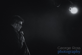 event photography: comedian at a microphone facing a spotlight