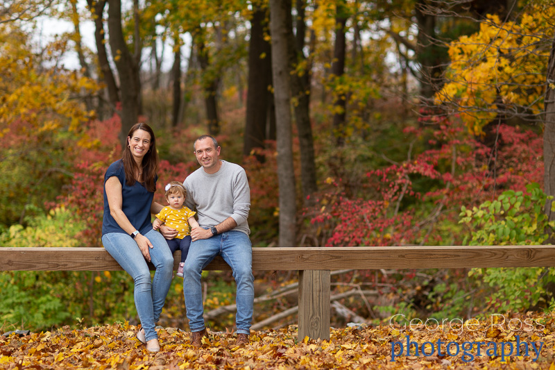 A rhode island family portrait in front of beautiful fall foliage.