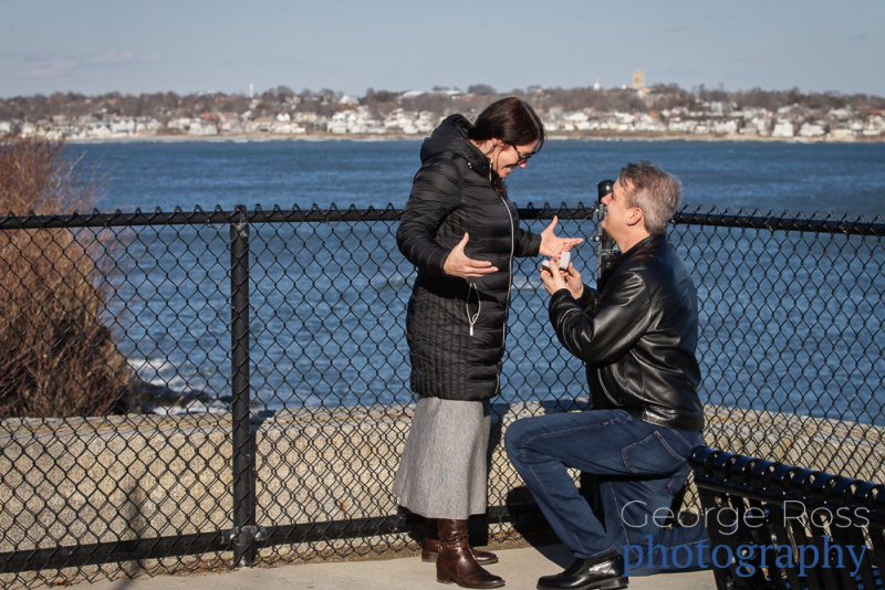 man on his knee proposing to his fences on the cliff walk, newport, rhode island