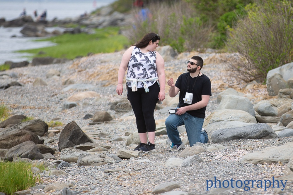 a man kneeling to propose on a beach in colt state park, rhode island