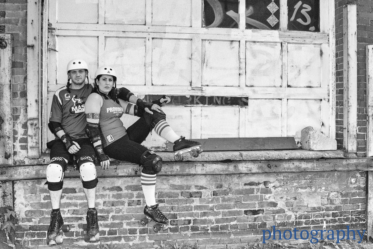 a roller derby couple agains an old garage door