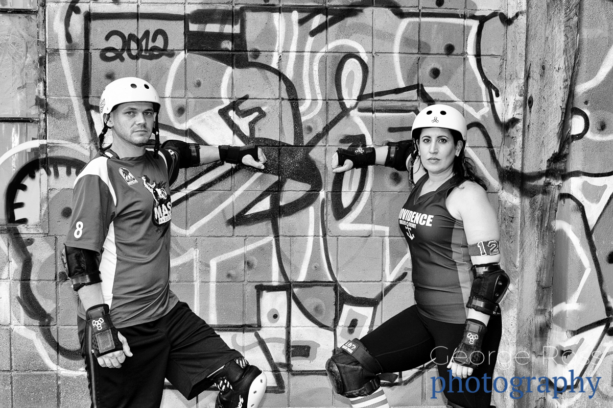 a roller derby couple in front of graffiti