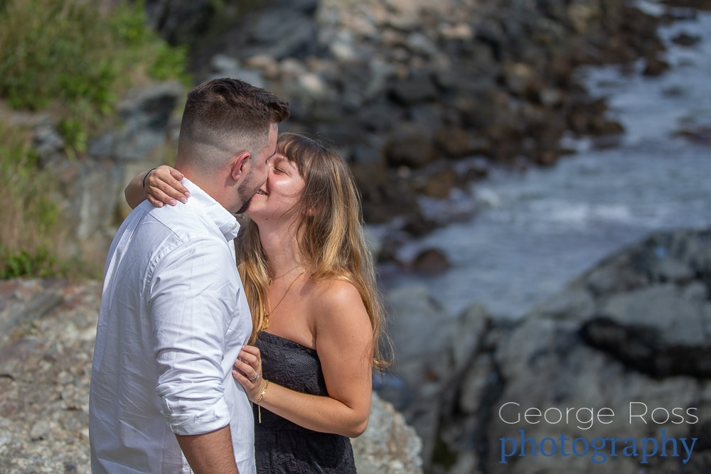A couple kiss after a surprise proposal on newport, rhode island's cliff walk at the 40-steps